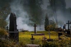 Un cimitero antico nella nebbia e nella luce della luna fotografia stock libera da diritti