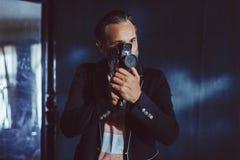 Un cineasta barbudo del hombre con una cámara del vintage en sus manos fotos de archivo