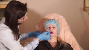 Un cirujano plástico comprueba la condición del labio paciente del ` s en una clínica privada almacen de metraje de vídeo