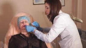 Un cirujano plástico hace un masaje del labio paciente del ` s en una clínica privada almacen de video