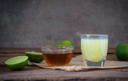 un citron de chaux avec du jus et le miel en verre transparent avec le sac Photographie stock libre de droits