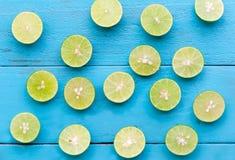 un citron de chaux sont demi coupe sur le fond en bois bleu Photos stock
