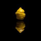 Un citron jaune d'isolement coupé en tranches sur le fond réfléchi noir Images libres de droits