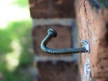 Un clavo curvado pegado en una pared de ladrillo fotografía de archivo