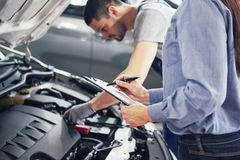 Un client de mécanicien et de femme d'homme regardent le capot de voiture et discutent des réparations images libres de droits
