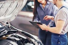 Un client de mécanicien et de femme d'homme regardent le capot de voiture et discutent des réparations image libre de droits