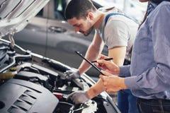 Un client de mécanicien et de femme d'homme regardent le capot de voiture et discutent des réparations image stock