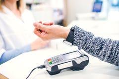 Un client effectuant le paiement sans fil ou sans contact utilisant le smartwatch photographie stock libre de droits