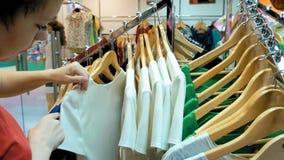Un client féminin passe en revue par les tissus Photos stock