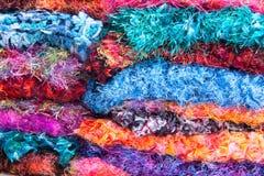 Un closuep de las bufandas coloridas apiladas del ganchillo de la pestaña y de la piel de la diversión Fotos de archivo libres de regalías
