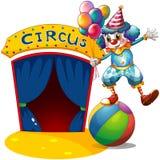 Un clown avec des ballons équilibrant au-dessus d'une boule Photographie stock libre de droits