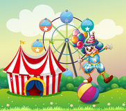 Un clown équilibrant au-dessus d'une boule gonflable au carnaval Image libre de droits