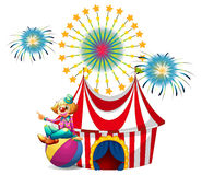 Un clown s'asseyant au-dessus de la boule au carnaval Image libre de droits