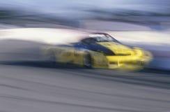 Un coche amarillo en la raza de Toyota Grand Prix en la serie de mundo del coche de Indy en Long Beach, CA Fotos de archivo libres de regalías