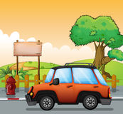 Un coche anaranjado a lo largo de la calle con un letrero de madera Foto de archivo