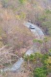 Un coche blanco lento baja la colina Fotos de archivo