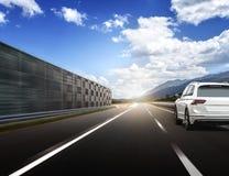 Un coche blanco que acomete a lo largo de una carretera de alta velocidad en el sol Imagen de archivo libre de regalías