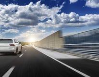 Un coche blanco que acomete a lo largo de una carretera de alta velocidad en el sol Fotografía de archivo