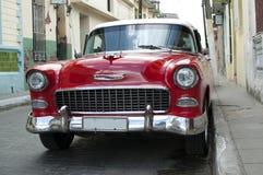 Un coche clásico americano rojo parqueó en una calle Foto de archivo