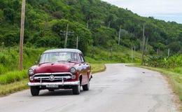 Un coche clásico rojo drived en el camino imagen de archivo