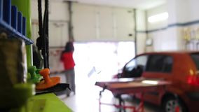 Un coche conduce en un taller de reparaciones del coche, tecnología de PDR, dos hombres va a reparar el coche, un garaje Abolladu metrajes