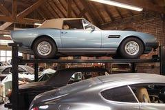 Un coche convertible cobrable del vintage clásico en la elevación en un taller de reparaciones fotografía de archivo libre de regalías