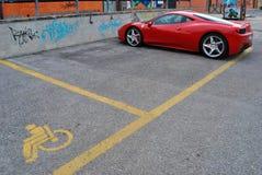 Un coche de Ferrari en una zona de estacionamiento discapacitada Fotos de archivo libres de regalías