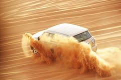 Un coche de la impulsión de 4 weel en la acción en un viaje del safari del desierto en Dubai imagenes de archivo