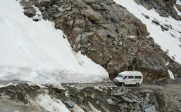 Un coche del viaje que corre en el camino de la nieve en Khardungla, la India Imagen de archivo libre de regalías