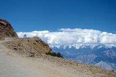 Un coche en el camino de la mucha altitud del paso del La de Khardung de Himalaya Imágenes de archivo libres de regalías