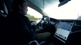 Un coche está siendo conducido por un hombre con una tableta en sus manos almacen de metraje de vídeo