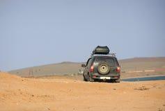 Un coche está conduciendo a través de las arenas Imagen de archivo libre de regalías