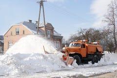Un coche grande con una paleta despeja el camino de la nieve El equipo especial del cargo anaranjado está luchando con los elemen fotografía de archivo