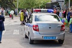 Un coche policía que se escabulle lentamente a través de la muchedumbre de celebra de la gente Imagen de archivo