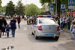 Un coche policía que se escabulle lentamente a través de la muchedumbre de celebra de la gente Imagen de archivo libre de regalías