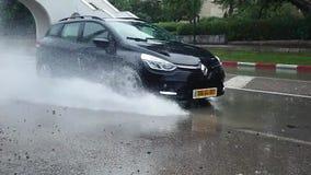 Un coche que salpica el agua de un charco del agua metrajes