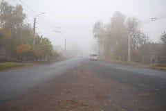 Un coche que se mueve a lo largo del camino en niebla fotografía de archivo