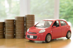 Un coche rojo sobre muchas monedas apiladas Fotografía de archivo libre de regalías