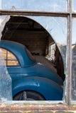 Un coche viejo de Morris Minor a través de la ventana quebrada de un garaje fotos de archivo