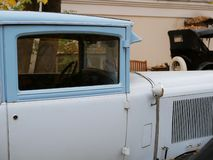 Un coche viejo en la yarda que se cubre con las hojas de arce amarillas fotos de archivo