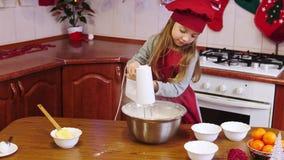 Un cocinero de la muchacha que mezcla con el mezclador eléctrico una pasta en el cuenco almacen de metraje de vídeo
