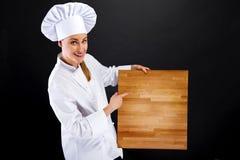 Un cocinero de sexo femenino llevando a cabo a los tableros de madera Imagenes de archivo