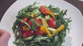 Un cocinero de sexo femenino se está preparando para servir una ensalada del arugula, de los tomates y de las pimientas dulces Pl metrajes