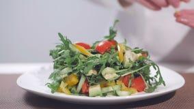 Un cocinero de sexo femenino se está preparando para servir una ensalada del arugula, de los tomates y de las pimientas dulces Pl almacen de metraje de vídeo