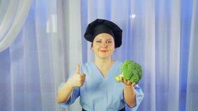 Un cocinero de sexo femenino sonr?e, se sostiene en su br?culi de la mano y clase de las demostraciones almacen de metraje de vídeo