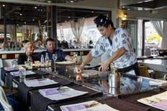 Un cocinero del teppanyaki que cocina en un teppan de gas Imagen de archivo