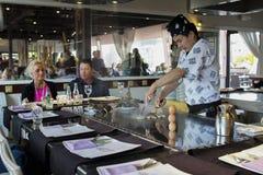 Un cocinero del teppanyaki que cocina en un teppan de gas en un asador japonés Imagen de archivo