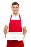 Un cocinero en el uniforme rojo que le ofrece un rectángulo de la pizza fotos de archivo libres de regalías