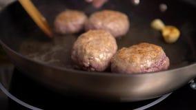 Un cocinero fríe las chuletas en una sartén, ajo se fríe cerca metrajes