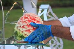 Un cocinero que arregla una escultura del melón para un partido, una recepción, una boda o una celebración Imagen de archivo